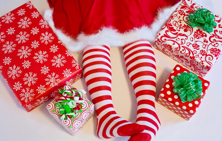 Picture of Mrs Claus legs in red striped tights surrounded by presents