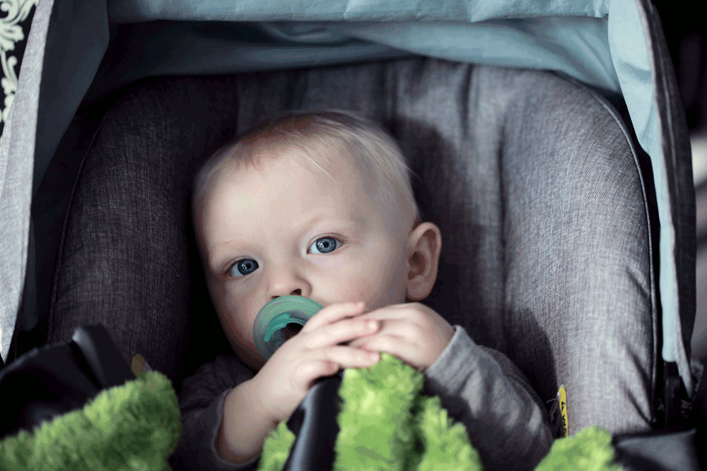 Picture of baby in car seat with pacifier and blanket