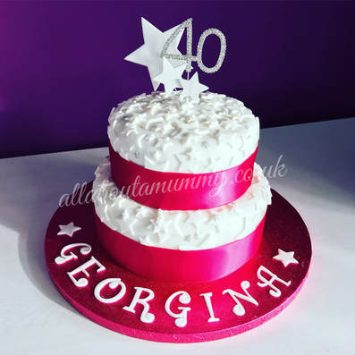 Picture of a pink 40th birthday cake. Two tiers covered in stars with a glittery 40 topper.